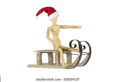 A wooden doll is posing on a sleigh and wearing a santa hat