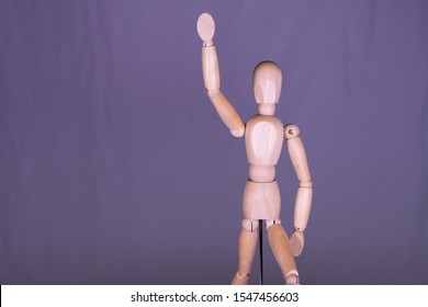 wooden doll puts a hand up to report something - pick me!