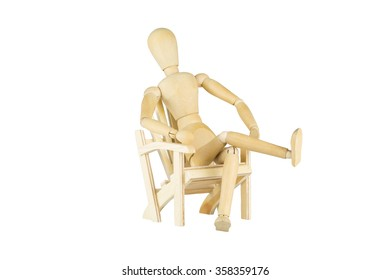 A wooden doll is sitting on a wooden miniature chair over white background