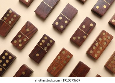 Wooden domino tiles on beige background, flat lay