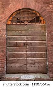 Wooden door and brick wall in Italy