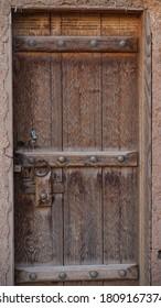 The wooden door built into mud wall - Old traditional wooden door in Shaqra, Riyadh, Saudi Arabia