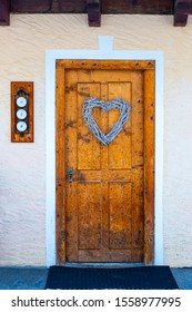 wooden door with christmas decorations, intertwined wooden heart