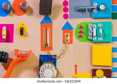 Wooden door decorated with colorful locks, latches, switches and doorbells - Shutterstock ID 536212699