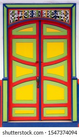 Wooden door, decorated with panels with lines and curves, in vibrant colors in Filandia, Quindío, Colombia