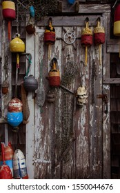 Wooden door with fishnets and lobster buoys hanged on wall, New England