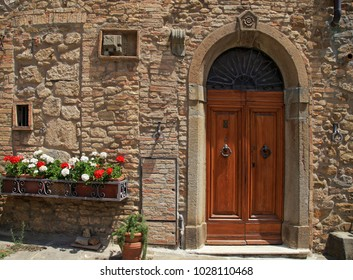 Wooden door with flowers in old Italian house in a small tuscan town, Tuscany, Italy.