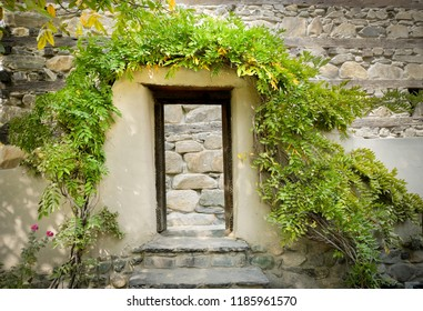 Wooden door frame gate covered with trees in front of stone retaining wall outside the Shigar fort. Skardu, Baltistan, Pakistan.