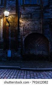 Wooden door and lamp in a dark street in Tallinn old town.