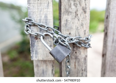A wooden door locked with a chain and padlock