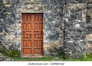 A wooden door with many panels is found in an old stone mission wall in San Antonio, Texas.