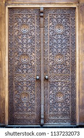 Wooden door in muslim temple with floral pattern and arabesques. Closed vintage gate in a turkish mosque with orient ornament in arabic style. Oriental tradition of wood carving in Turkey.