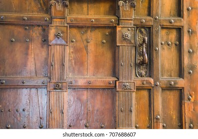 An wooden door with an old decoration on the city street at the entrance to the courtyard.
