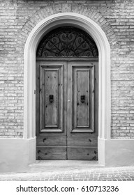 Wooden door in an old Italian house, black and white.