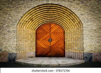 Wooden door on brick wall church in Copenhagen