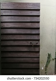 A wooden door with a padlock hanging on the handle and a creeping tree climbing on a wall