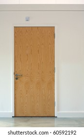 Wooden door set in a white wall