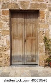 wooden door in stone wall and flowerpot, mediterranean style