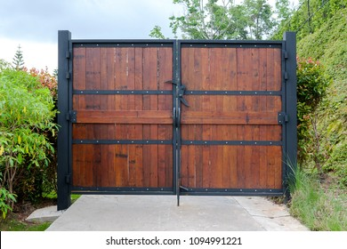 Wooden door swing on a large black steel frame that connects the house and the garden. Ideas for Home Design and Decoration.