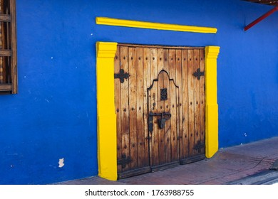 Eine Holztür, die zu einem blau gestrichenen Haus gehört und sich in Kolumbien befindet.