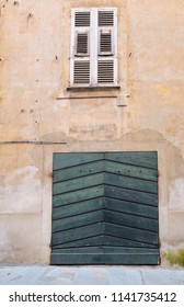 A wooden door and a window closed with shutters in the old time wall