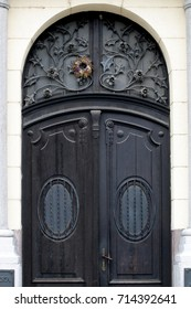 Wooden door with window decorated with wrought iron