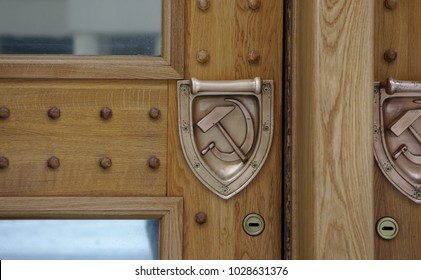 Wooden doors with beautiful metal handles. Door handles with symbols of the Soviet Union.