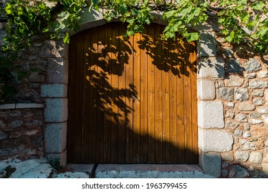 Wooden doors to greek house with grapevine - Shutterstock ID 1963799455