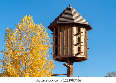 The wooden dovecote on the background of the blue sky. A large pigeon loft or dovecote.