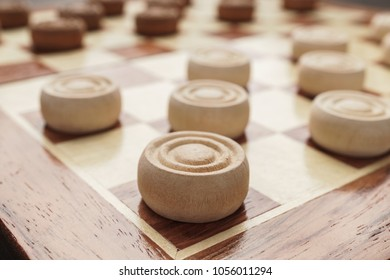 wooden draughts board game on brown table