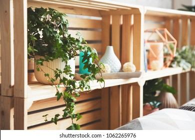 Wooden drawer shelves with decor. Creative head of the bed, shelves for decor in the loft style or Scandinavia. Trend elements of the interior. Pot with ivy