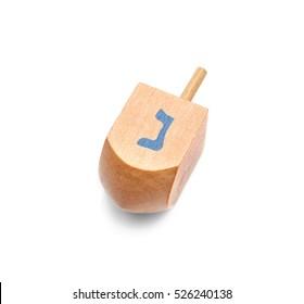 Wooden dreidel for Hanukkah on white background