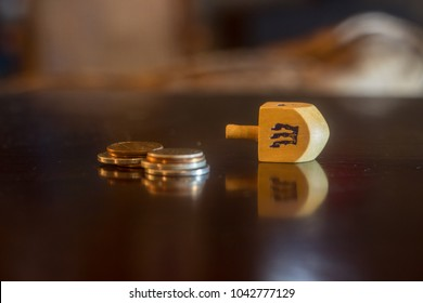Wooden dreidel next to a scattered pile of American coins