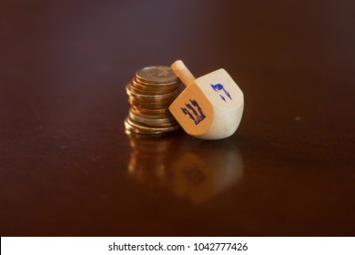 Wooden dreidel resting on a stack of American coins