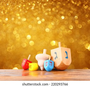 wooden dreidels (spinning top) for hanukkah jewish holiday over glitter gold background