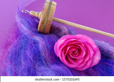 Wooden Drop Spindle (Top Whorl) On A Piece Of Roving In Blue, Pink, And Purple With A Delicate, Pink Flowerhead Of A Rose Against A Purple Background