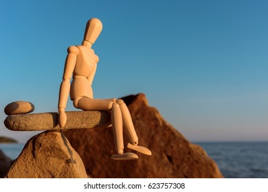 Wooden dummy in balance on the stone on seashore
