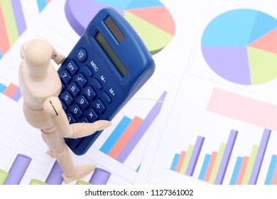 Wooden dummy with calculator on color chart printed documents background