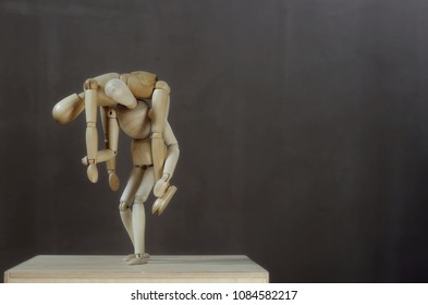 a wooden dummy carries a sick dummy on his shoulder. Grey background. Room for text. Horizontal photo.