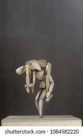 a wooden dummy carries a sick dummy on his shoulder. Grey background. Room for text. Vertical photo.
