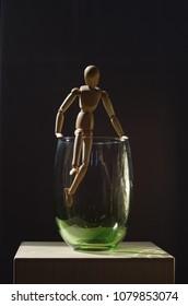 Wooden dummy climbing over a green glass vase. Backlight. Vertical photo.
