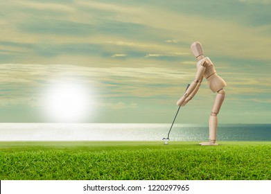 Wooden dummy doll, Wood figure putt golf ball on green  The concept of sports tourism and leisure.