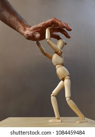 a wooden dummy fights against a human hand trying to grasp it. Grey background. Vertical photo.