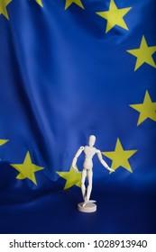 Wooden dummy figurine on European flag. Closeup