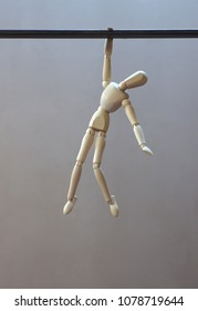 Wooden dummy hanging by a hand, about to fall. Vertical. Gray background.