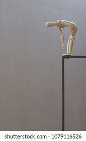 Wooden dummy on metal scaffold bent forward looking down towards the void; vertical; gray background.