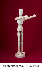 a wooden dummy posing with arms in front with red background