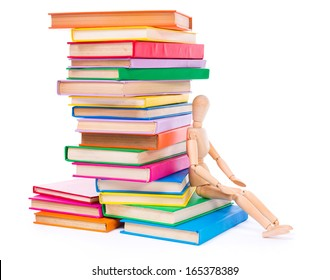 Wooden dummy puppet sitting on the bottom of stacked colorful books