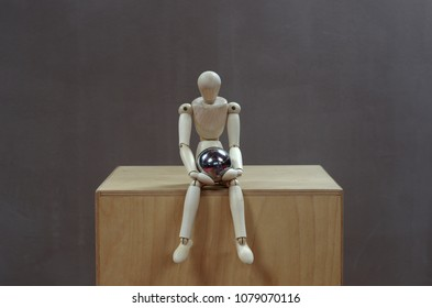 Wooden dummy sitting on a wooden box looking at a steel ball on his lap in a pensive attitude. Grey background.