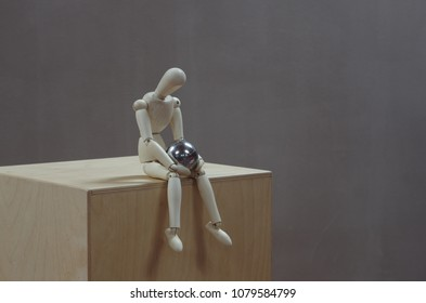 Wooden dummy sitting on a wooden box looking at a steel ball on his lap in a pensive attitude. Grey background. Horizontal photo. 3/4 view. Room for text.